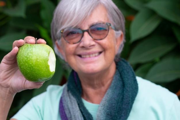 Close-up van een groen gebeten appel bedrijf door een senior lachende vrouw. concept van gezond eten en dieet