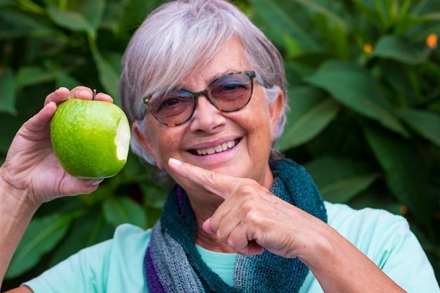 Close-up van een groene gebeten appel die door een wazige senior lachende vrouw wordt vastgehouden. concept van gezond eten en dieet