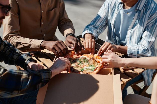 Close-up van een groep jonge mensen die buiten van pizza genieten, scène verlicht door zonlicht, kopieer ruimte