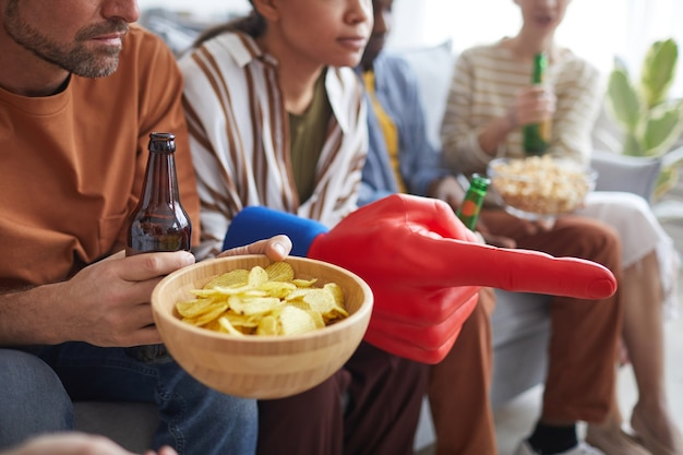 Close-up van een groep mensen die snacks en ventilatorspullen vasthoudt terwijl ze samen naar een sportwedstrijd kijken, kopieer ruimte