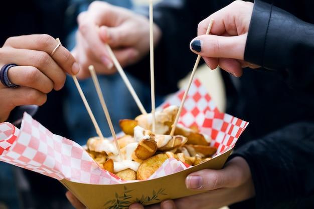 Close-up van een groep vrienden die een bezoek brengt aan de markt en aardappelen op straat eet.