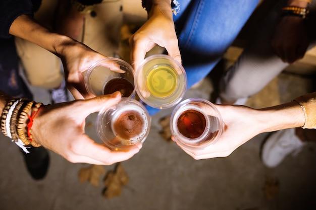 Close-up van een groep vrienden die roosteren met bier in de eetmarkt op straat.