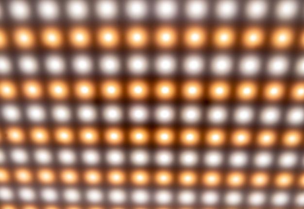Close-up van een groot paneel met heldere koude wazige lichten, lichtgevende knoppen bij de vervaardiging van radioproducten of in een disco. equalizer en fabrieksuitrustingsconcept