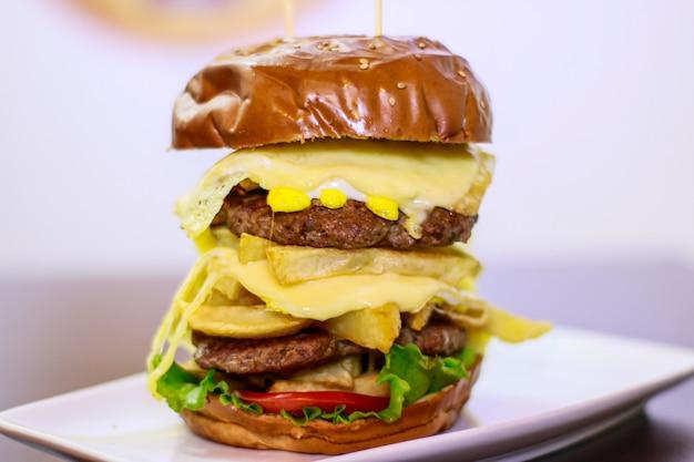 Close-up van een grote dubbele hamburger op porseleinen bord en witte achtergrond