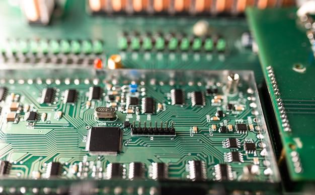 Close-up van een grote groene microschakeling en lichtgevende panelen in een fabriek voor radio-onderdelen. complex elektronisch apparatuurconcept in een fabriek