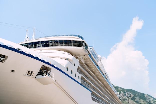 Close-up van een grote witte afgemeerde cruiseschip op een steiger dichtbij de oude stad van kotor in montenegro