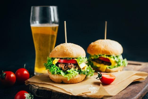 Close-up van een hamburger met vlees op een grilltomaat en greens op zwart