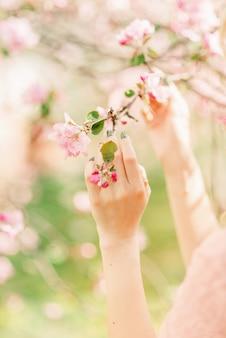 Close-up van een hand die een bloeiende tak houdt. lente tuin