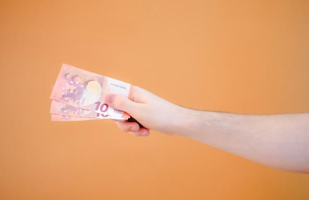 Close-up van een hand die een bundel van dertig euro geeft op een oranje achtergrond