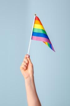 Close-up van een hand die een kleine regenboogvlag golft tegen lichtblauw