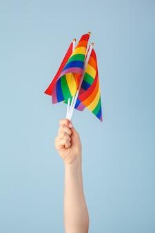 Close-up van een hand die een kleine regenboogvlag zwaait tegen een lichtblauwe achtergrond