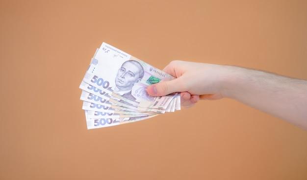 Close-up van een hand die een pakje van drieduizend hryvnia geeft op een oranje achtergrond