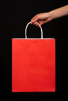 Close-up van een hand die een rode het winkelen zak op een zwarte achtergrond houdt