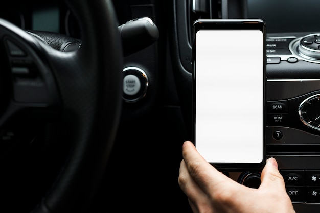 Close-up van een hand die slimme telefoon houdt die het witte lege scherm in de auto toont