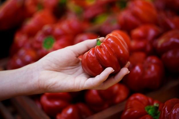 Close-up van een hand kiest een rode peper op de plank in een groente winkel