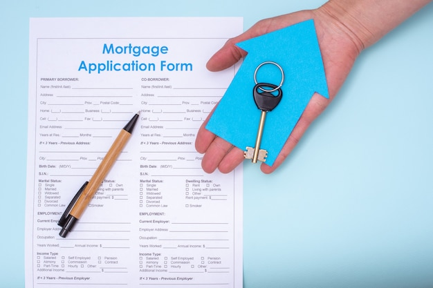 Close-up van een hand met een sleutel op een blauw papieren huis over een hypotheekaanvraag en een pen, bovenaanzicht, kopieerruimte, plat lag, blauwe achtergrond. aankoop van onroerend goed, verhuurconcept