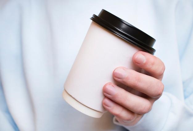 Close-up van een hand van de man met een koffiekopje naast een raam met een groene achtergrond buiten