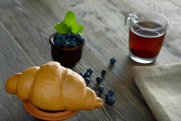 Close-up van een heerlijk vers gebakken croissant voor een kopje thee en een kom met bosbessen