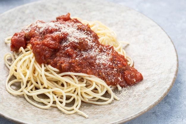 Close-up van een heerlijke pasta met tomatensaus en geraspte kaas in een bord