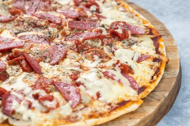 Close-up van een heerlijke pizza met gesneden worstjes en gesmolten kaas op een bord onder de lichten