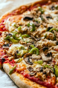 Close-up van een heerlijke zelfgemaakte italiaanse pizza met kaas, tomaten, champignons en groene paprika