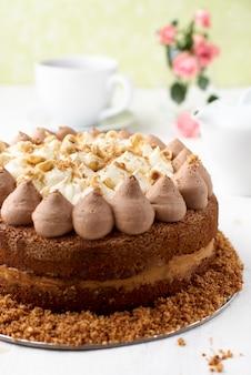 Close-up van een hele chocoladelaagcake met karamel en notentopping op een licht houten oppervlak.
