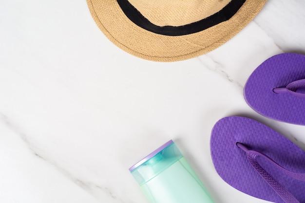 Close-up van een hoed, flip-flops en zonnescherm.