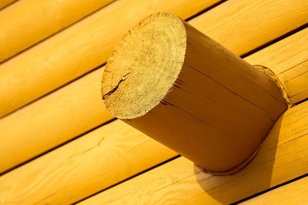 Close-up van een hoek van een geel blokhuis met ronde logboeken