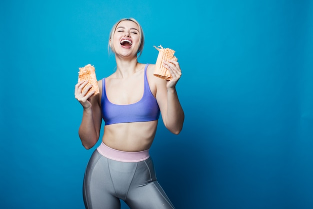 Close-up van een hongerige vrouw die een grote sandwich eet