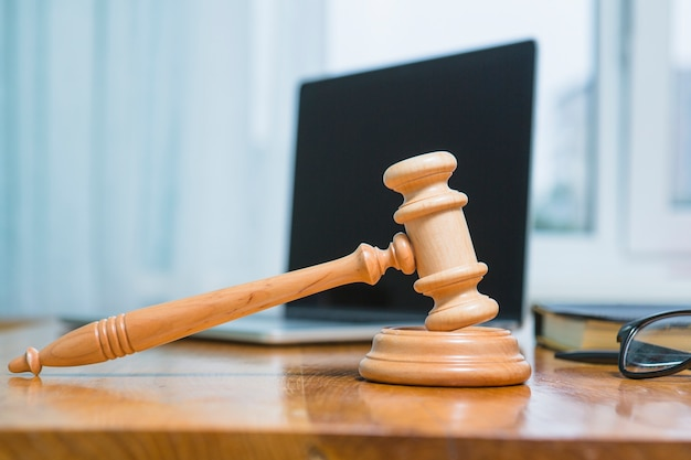 Close-up van een houten hamer op bureau in rechtszaal