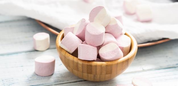 Close-up van een houten kom vol roze en witte marshmallows met wat verspreid over een wit tafelkleed, een donker dienblad en een witte houten tafel.
