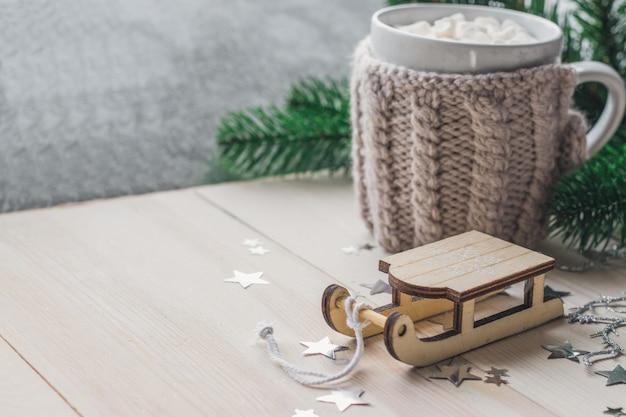 Close-up van een houten slee ornament met een mok marshmallows op de houten tafel
