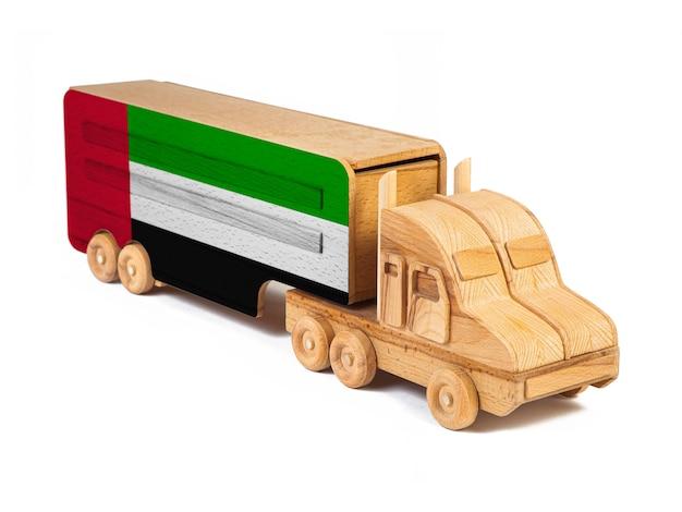Close-up van een houten speelgoed vrachtwagen met een geschilderde nationale vlag verenigde arabische emiraten.