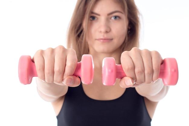 Close-up van een jong atletisch meisje met uitgestrekte handen met roze halters sport