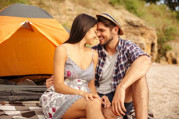 Close up van een jong gelukkig mooi paar zittend bij de tent op het strand en zoenen