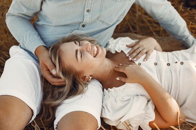 Close up van een jong koppel zit op het tarweveld. mensen zitten op hooiberg op weide en omhelzen. Gratis Foto