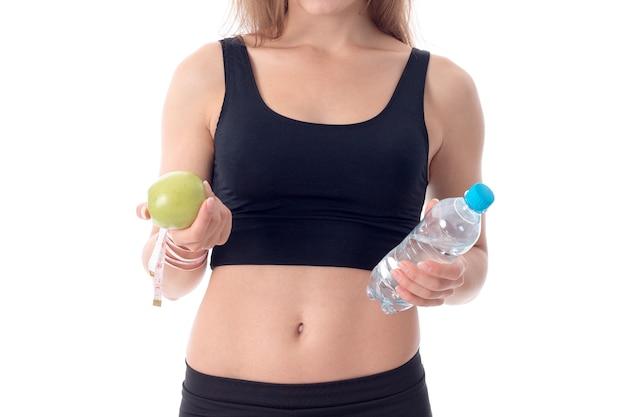 Close-up van een jong meisje dat haar een appel in de ene hand laat zien en de andere met een fles water