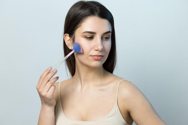 Close-up van een jong meisje in een lichte top op een witte achtergrond die een gezichtsmake-up maakt