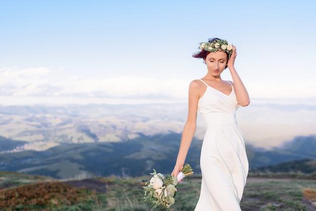 Close-up van een jong meisje in een witte jurk met een krans op zijn hoofd en een boeket bloemen buitenshuis