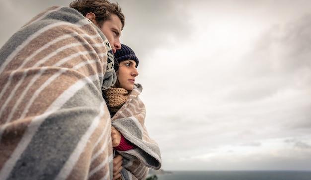 Close-up van een jong mooi stel onder deken op een koude dag op zoek naar de zee met de donkere bewolkte lucht op de achtergrond