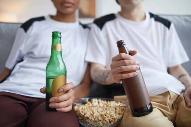 Close-up van een jong stel dat thuis tv of films kijkt met de nadruk op popcorn en bierflesjes, kopieer ruimte