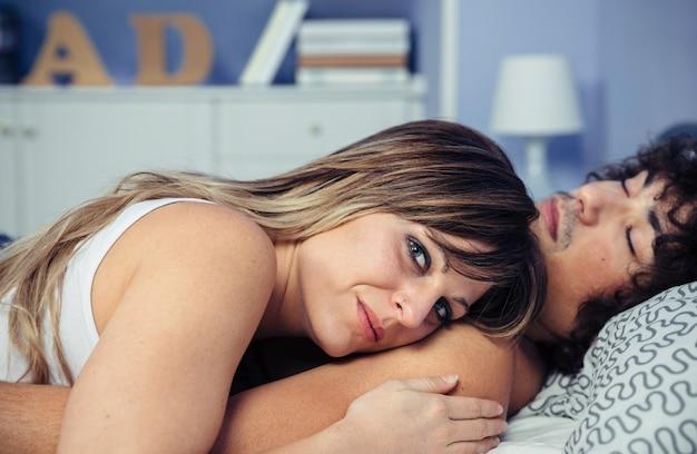 Close-up van een jong verliefd stel omarmen samen ontspannen liggend over een bed met de vrouw die over de borst van de man rust. liefde en paar relaties concept.