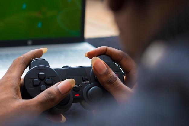 Close-up van een jonge afrikaanse jongen met gamepad, consolepad tijdens het spelen van een game