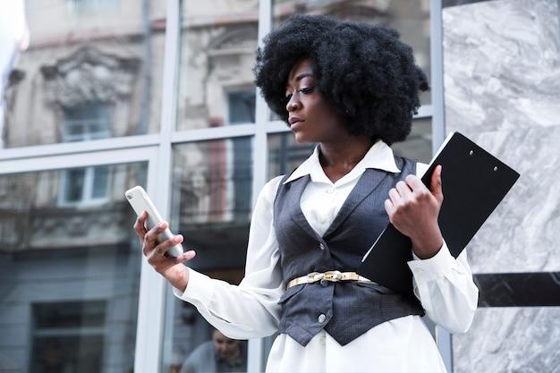 Close-up van een jonge afrikaanse zakenvrouw klembord houden met behulp van mobiele telefoon