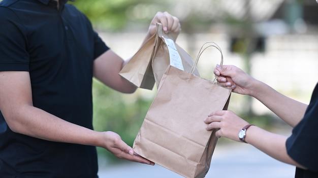 Close-up van een jonge aziatische bezorger die een papieren zak met eten geeft aan een vrouwelijke klant bij de huisdeur.