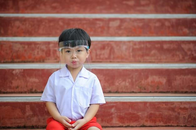 Close-up van een jonge aziatische jongen die een gezichtsscherm draagt tegen het coronavirus covid-19