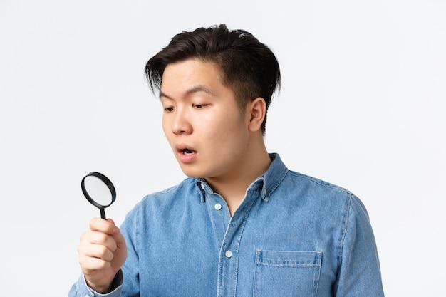 Close-up van een jonge aziatische man die nieuwsgierig en gefocust op zoek is naar iets dat door een vergrootglas kijkt...