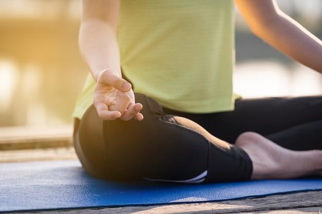 Close-up van een jonge aziatische mooie vrouw die yoga beoefent en mediteert in de lotushouding buiten naast het meer in de ochtend voor ontspanning en gemoedsrust. harmonie en meditatie concept.