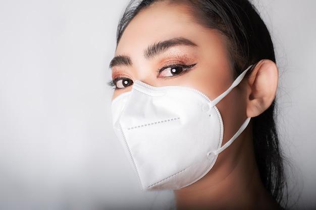 Close-up van een jonge aziatische vrouw die een medisch masker opzet n95