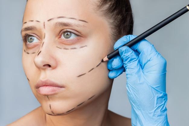 Close-up van een jonge blanke vrouw met markering op haar gezicht de gehandschoende hand van de dokter maakt sporen
